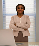 Happy smiling black businesswoman standing by  her desk. The woman is wearing a smart looking business suit and she has her arms crossed in front of her.